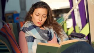 Calm girl wearing warm scarf while reading book outdoors