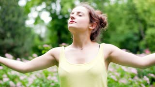 Calm girl with closed eyes standing in the park and doing yoga