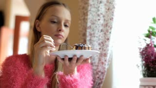 Calm, thoughful girl sitting in the cafe and eating delicious cake