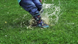 Child jumping into puddle, slow motion shot at 240fps