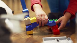 Child playing with blocks, closeup, steadycam shot, slow motion shot at 100fps
