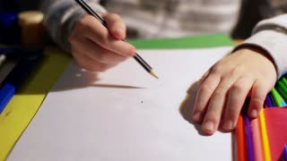 Child using pencil and doing lines on the sheet of paper