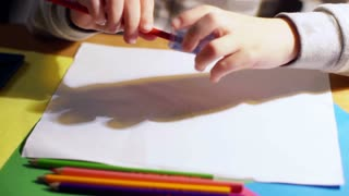 Child using sharpener and painting something on the paper