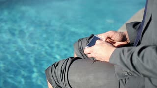Close up of businessman with cellphone sitting by swimming-pool