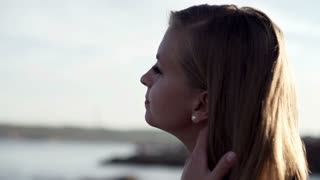 Close up of young woman standing on seashore, slow motion shot at 240fps