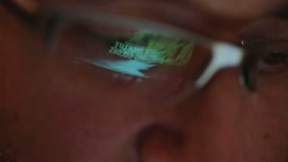 Closeup shot of man in glasses surfing internet at night
