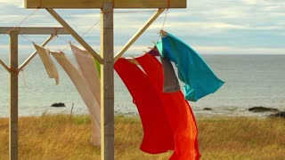 Colourful towels waving on wind by seashore, slow motion shot at 60 fps