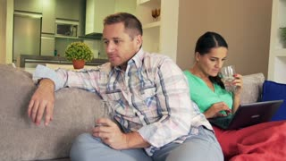 Couple after quarrel sitting on the sofa and man leaving flat, steadycam shot
