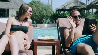 Couple chatting on tablet next to a swimming pool