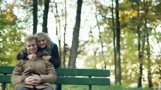 Couple cuddling and showing thumbs to the camera in the park