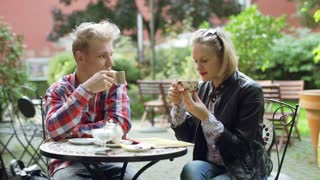 Couple drinking tea and chatting in the outdoor cafe