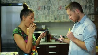 couple eating and using cellphone and tablet in the kitchen