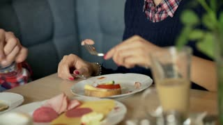 Couple eating breakfast in the cafe and girl feeding his boyfriend, steadycam sh
