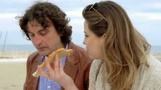 Couple eating pizza and talking at the sea, steadycam shot, slow motion shot at