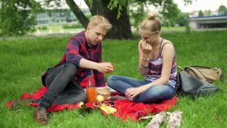 Couple feeding each other with strawberries and smiling to the camera