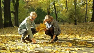 Couple gathering maple leaves in the autumnal park and throwing to the air