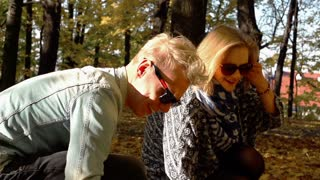 Couple gathering maple leaves in the park, steadycam shot, slow motion shot at 2