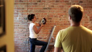 couple hanging a clock on the brick wall in their new flat