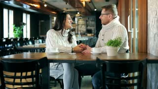 Couple holding hands and chatting in the restaurant