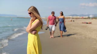 Couple in love and sad woman on the beach, steadicam shot