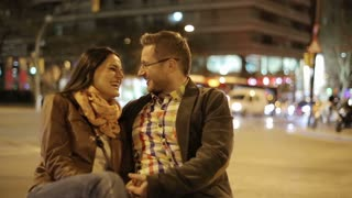 Couple in love sitting and talking in night city, steadycam shot