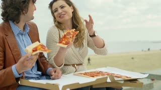Couple laughing and eating pizza on the beach, steadycam shot