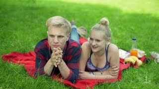 Couple lying on the blanket in the park and chatting