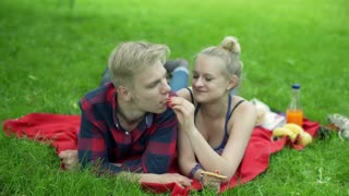 Couple lying on the blanket in the park and feeding each other with wafer-cake