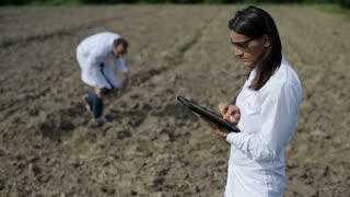 couple of scientists working with tablet in the field