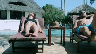 Couple relaxing on the sunbeds, steadycam shot
