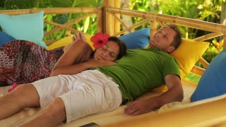 Couple resting together in exotic garden, steadycam shot