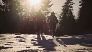 Couple run to the forest on deep snow, steady, slow motion shot at 240fps