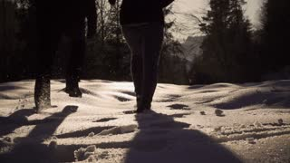 Couple running to the forest on snow, steady, slow motion shot at 240fps