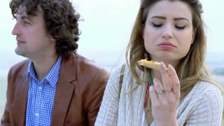 Couple sitting in silence and eating pizza, steadycam shot, slow motion shot