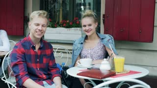 Couple sitting in the cafe and smiling to the camera