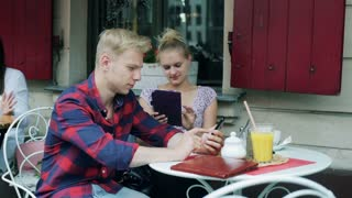 Couple sitting in the cafe and using modern technology