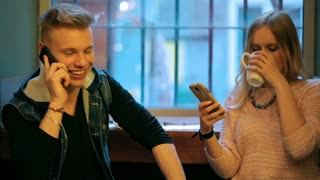 Couple sitting next to the window in the cafe and using smartphones