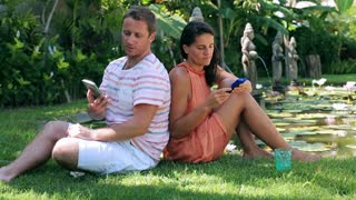 Couple sitting on grass in the garden and talking about cellphones