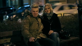 Couple sitting on the bench at night and doing funny faces