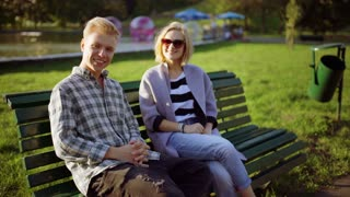 Couple sitting on the bench in the park and smiling to the camera