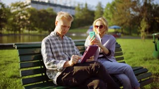 Couple sitting on the bench in the park and using electronics