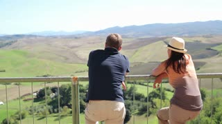Couple standing at view-point enjoying panorama of Toscana