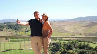 Couple standing at view-point of Toscana and taking a picture by smartphone