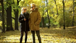 Couple standing in the autumnal park and chatting with each other