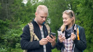 Couple standing in the forest and talking while using smartphones