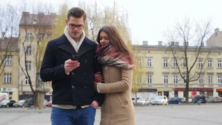 Couple standing on public square and man texting on smartphone