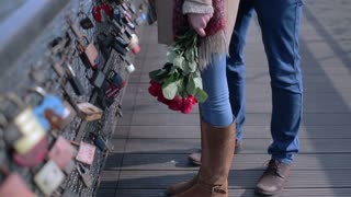 Couple standing on the bridge and woman smelling bunch of roses
