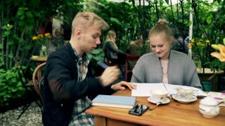 Couple studying together in the cafe and smiling to the camera