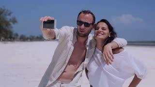 Couple taking photos on the beach