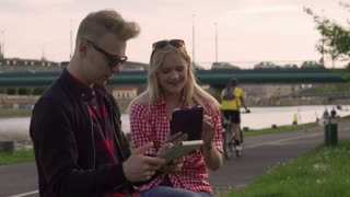 Couple talking and using tablets in the public place